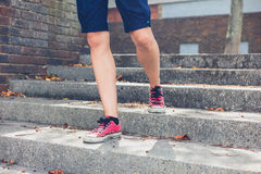 Legs of young woman walking down steps Stock Images