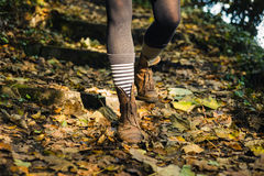 Legs of young woman walking down woodland slope Royalty Free Stock Photos