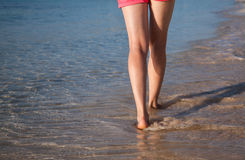 Legs of a young woman walking near the sea Stock Images