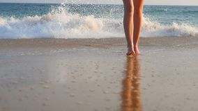 Legs of young woman walking from the ocean waves to the sand beach. Feet of unrecognizable girl in bikini stepping from stock video
