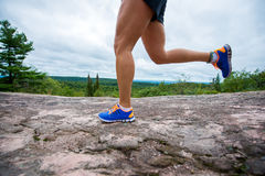 Legs of young woman wearing fitness clothing running across rocks with forest background Stock Images