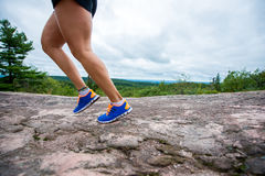 Legs of young woman wearing fitness clothing running across rocks with forest background Stock Photo