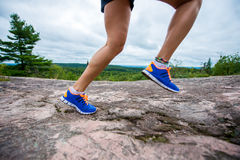 Legs of young woman wearing fitness clothing running across rocks with forest background Stock Photos