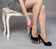 Legs of young woman wearing mini dress and high-heeled black sho Royalty Free Stock Photography