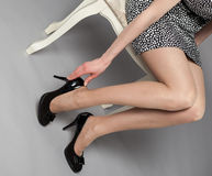 Legs of young woman wearing mini dress and high-heeled black sho Stock Photography