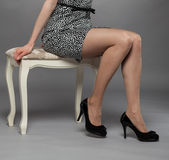Legs of young woman wearing mini dress and high-heeled black sho Stock Images