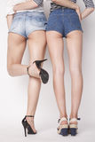 Legs of young women, pair  butts in jeans shorts Royalty Free Stock Images