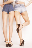 Legs of young women, pair butts in jeans shorts Stock Photo