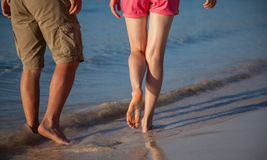Legs of a youngcouple walking along the seacoast Stock Photo