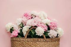Legt de modieus stro rustieke zak met witte en roze pioenen op vlak pastelkleur roze document, met exemplaarruimte Hello-de lente