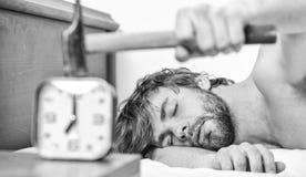 Legt het mensen gebaarde geërgerde slaperige gezicht hoofdkussen dichtbij wekker Kerel die met hamerwekker het bellen kloppen ond stock foto