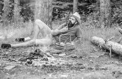 Legt mensen gebaarde hipster dichtbij kampvuur na dag die of paddestoelen wandelen verzamelen De mens heeft snack of picknick in  royalty-vrije stock fotografie
