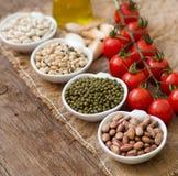 Legumbres en cuencos, tomates, ajo y aceite de oliva en la tabla de madera Imagen de archivo libre de regalías