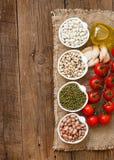 Legumbres en cuencos, tomates, ajo y aceite de oliva en la tabla de madera Fotografía de archivo