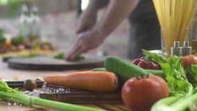 Legume fresco na mesa de cozinha Cozinheiro do cozinheiro chefe que corta as hortaliças no fundo do alimento Ingrediente fresco p filme