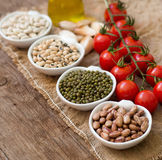 Legumes in bowls, tomatoes, garlic and olive oil on wooden table Royalty Free Stock Image
