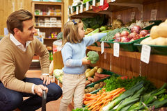 Legumes frescos de And Daughter Choosing do pai na loja da exploração agrícola Foto de Stock Royalty Free
