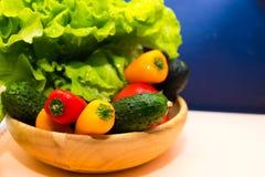 Legumes frescos e ervas em uma bacia de madeira em um fundo azul branco Alimento saudável da salada Alimento perdido do peso Imagem de Stock Royalty Free