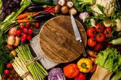Legumes frescos em torno da placa de corte de madeira Fotos de Stock