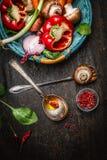 Legumes frescos na cesta, cozinhando colheres com óleo e especiarias no fundo de madeira rústico, vista superior Imagens de Stock Royalty Free
