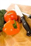 Legumes frescos na placa de estaca com faca imagem de stock