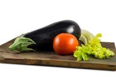 Legumes frescos na placa de madeira: tomate, beringela e aipo Fotos de Stock