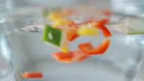 Legumes frescos que espirram na água no movimento lento filme