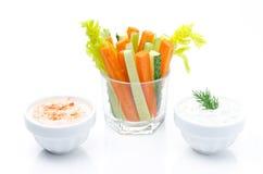 Legumes frescos sortidos em um vidro e em um molho do iogurte dois isolados Foto de Stock