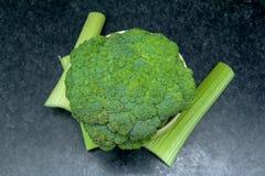 Legumes frescos verdes brócolis inteiros em uma bacia com aipo na tabela Foto de Stock