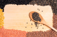 Legumes lentils and a wooden spoon Stock Photos