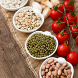 Leguminosa, tomates, alho e azeite na tabela de madeira Foto de Stock