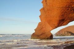 Legzira arc on sea beach. Legzira beach stone arch in sunset beautiful light. Red rocks on ocean shore, Atlantic. Legzira arcs near Sidi Ifni village in Morocco Royalty Free Stock Photo