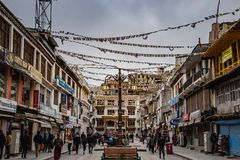 Crowd of people in Main Bazar market, Leh City, India. Leh, India : April 2019 - Crowd of people with Buddhist Tibetan prayer flag and lot of survinior shop on royalty free stock images