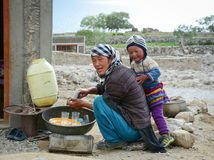 Tibetan woman with her son  in Nubra, India. Leh, India - Jul 21, 2015. A Tibetan woman with her son at a village in Nubra Valley, India. 65% of children attend Stock Photos