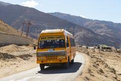 Leh, la India - 12 de abril de 2016: Un paso del funcionamiento del autobús escolar el camino en el camino de Ladakh-Leh de la mu Foto de archivo