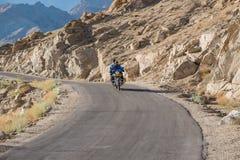 Leh, la India - julio 12,2014: Montar a caballo del motorista en el camino Fotos de archivo