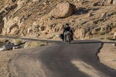 Leh, la India - julio 12,2014: Montar a caballo del motorista en el camino Foto de archivo libre de regalías