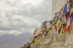 Tibetan prayer colored flags with mantras on a white temple wall against the backdrop of snowy mountains royalty free stock photo