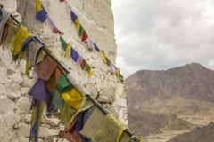 Tibetan prayer colored flags with mantras on the white wall of the temple against the backdrop of the mountains. Leh, Ladakh, Jammu and Kashmir/ India - 13.08 royalty free stock photography