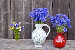 2 Lehmkrüge und -Trinkglas voll Kornblumen, Butterblumeen und Gänseblümchen Lizenzfreies Stockfoto