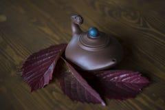 Lehmteekanne mit Drachekopf in der chinesischen Art mit Blättern der roten Traube am dunklen hölzernen Hintergrund lizenzfreie stockfotos