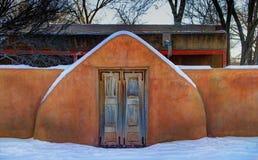 Lehmziegelmauer und Holztür im Schnee Stockbild