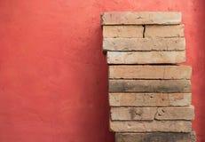 Lehmziegelsteinstapel über rotem Zementwandhintergrund Stockfotos