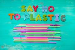 Lehnen Sie Plastik - bunte h?lzerne Buchstabephrase auf gr?nem h?lzernem Hintergrund mit Plastikstrohen, Draufsicht ab lizenzfreies stockfoto