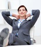 Lehnende Füße der Geschäftsfrau auf ihrem Schreibtisch Lizenzfreies Stockbild