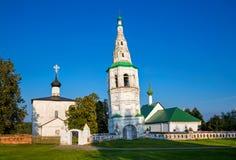 Lehnender Glockenturm und zwei Kirchen im Dorf von Kideksha Stockfotografie