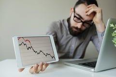 Lehnender Kopf des deprimierten Geschäftsmannes unterhalb des schlechten Börsediagramms Lizenzfreie Stockfotografie