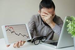 Lehnender Kopf des deprimierten Geschäftsmannes unterhalb des schlechten Börsediagramms Lizenzfreies Stockfoto