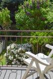 Lehnsessel auf dem Balkon vor dem Garten stockfoto
