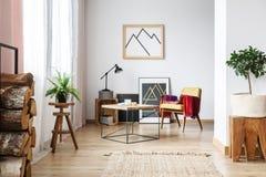 Lehnsessel, unbedeutendes Plakat und Brennholz stockfoto